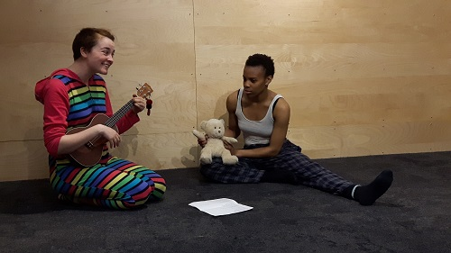 Photo of two people: one with a teddy bear, one strumming a ukulele