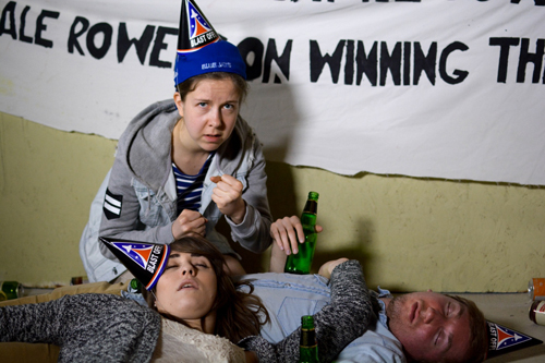 after-party scene, with two people passed out and a third with raised fists