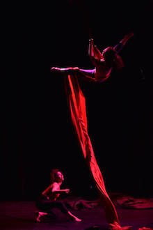 Photo of a performer in the air suspended by silks and another performer on stage looking up.