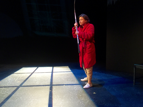 Melanie Lepp in a red robe holding a hockey stick