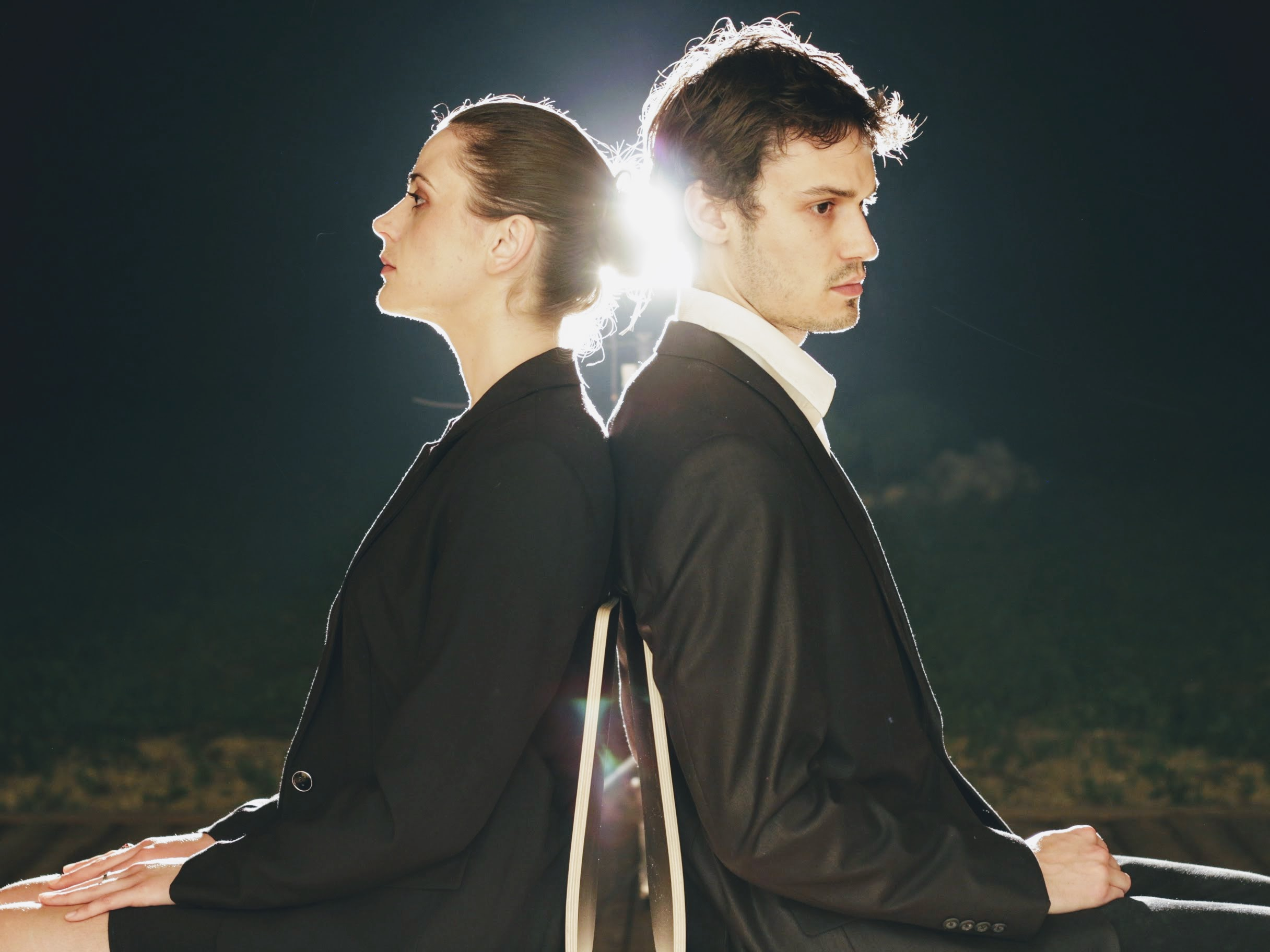 Anastasia Wells and Elliot Delage, sitting back to back with a light shining between them.
