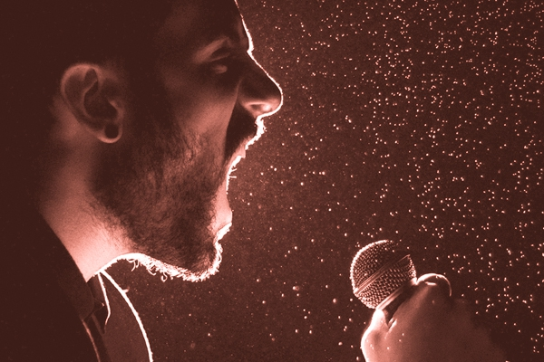 Image of a man hollering into a microphone