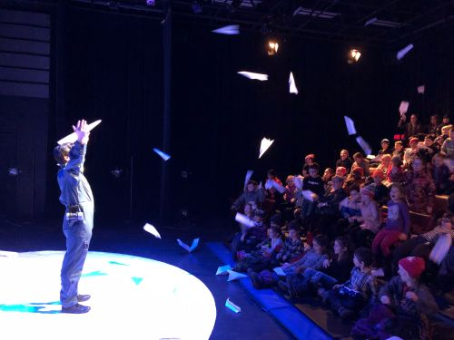 Photo of Richard Lam onstage with paper airplanes being thrown at him