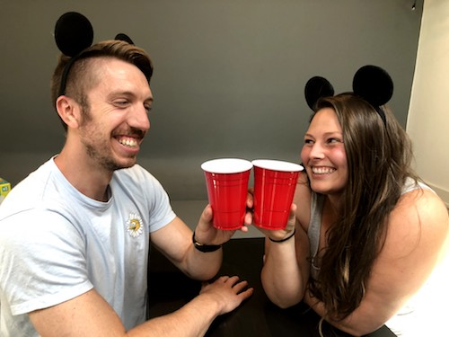 Photo of photo of Mike Wisniowski and Kimberly Dolan in BFFs - two smiling friends wearing Mickey Mouse ears toast each other with red solo cups.