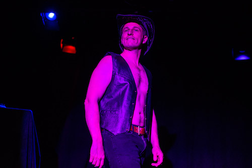 photo of DK Reinemer in Becoming Magic Mikeby Andrew Alexander - a shirtless white man in a leather vest and cowboy hat looks at the audience under purple stage lighting.