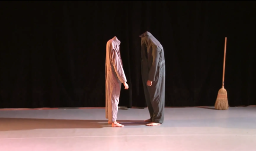 Photo of two dances facing each other wearing coveralls pulled up over their heads