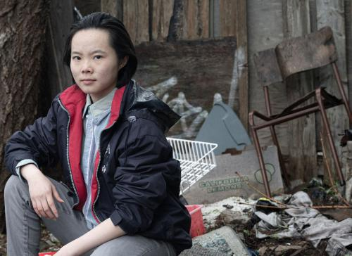 Photo of young adult sitting in front of pile of trash, promo photo for The Breath Between