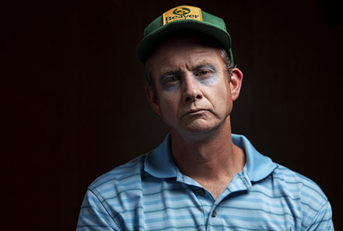 Man wearing pale make-up, a green ball cap, and a blue striped polo shirt stares at the camera, Footnote Number 12, SummerWorks