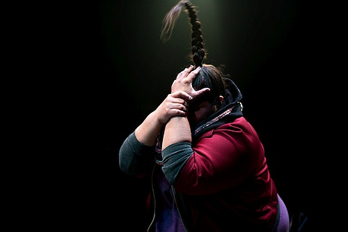 Photo of profile of a woman covering her face with both her hands, her long hair in a braid which stands straight up Yolanda Bonnell in bug