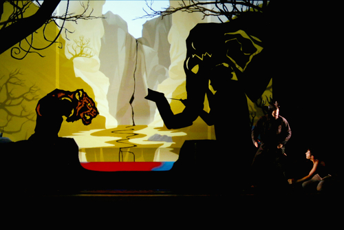 image of two people in the bottom right of a large set with a shadow of an elephant and a jaguar - from Jungle Book at YPT Photo of Matt Lacas and Levin Valayil and by Rick Miller.