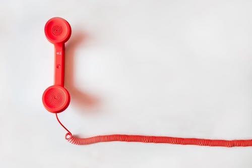 Photo of red phone handset with cord by Negative Space