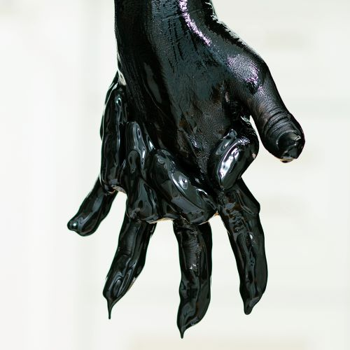 Picture of two hands clasping, covered in thick black paint