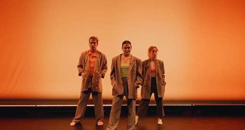 three people stand in beige suits on a stage against a peach coloured background