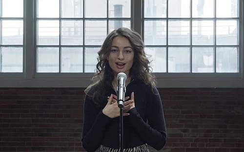Photo of a woman speaking into a microphone in a big industrial looking room