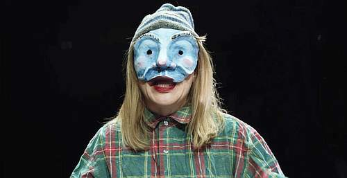 Photo of a person with long blond hair wearing a blue pottery mask over half their face