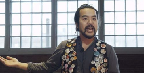 Photo of a man wearing a vest covered with button pinned all over it speaking to the camera