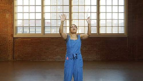 Woman standing with both arms held up in the air