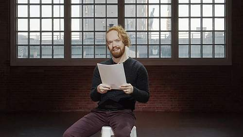 Photograph of a man sitting on a chair holding paper in front of him
