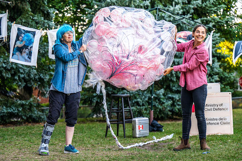 Photo of Kate Lushington and Natasha Greenblatt in an outside setting in a park, holding a clear bag filled with pink balloons between them in Apocalypse Play